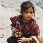 Little Girl Wearing Traditional Mayan Dress Holding Worry Dolls