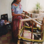 Guatemalan Weaver Utilizing a Yarn Winder to Wrap Yarn Around Pegs on Warping Board