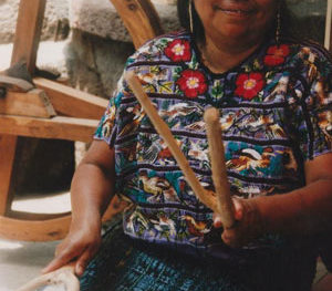 Guatemalan woman preparing raw cotton for weaving
