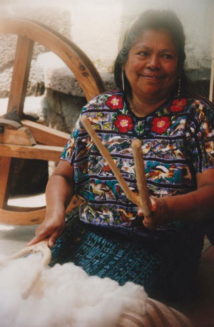 Guatemalan woman preparing raw cotton for weaving